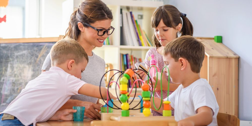 Preschool,Teacher,With,Children,Playing,With,Colorful,Wooden,Didactic,Toys