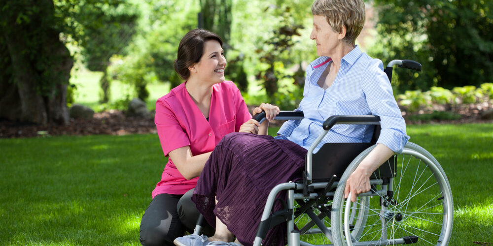 Happy,Senior,Woman,On,Wheelchair,With,Caring,Caregiver,Outdoors